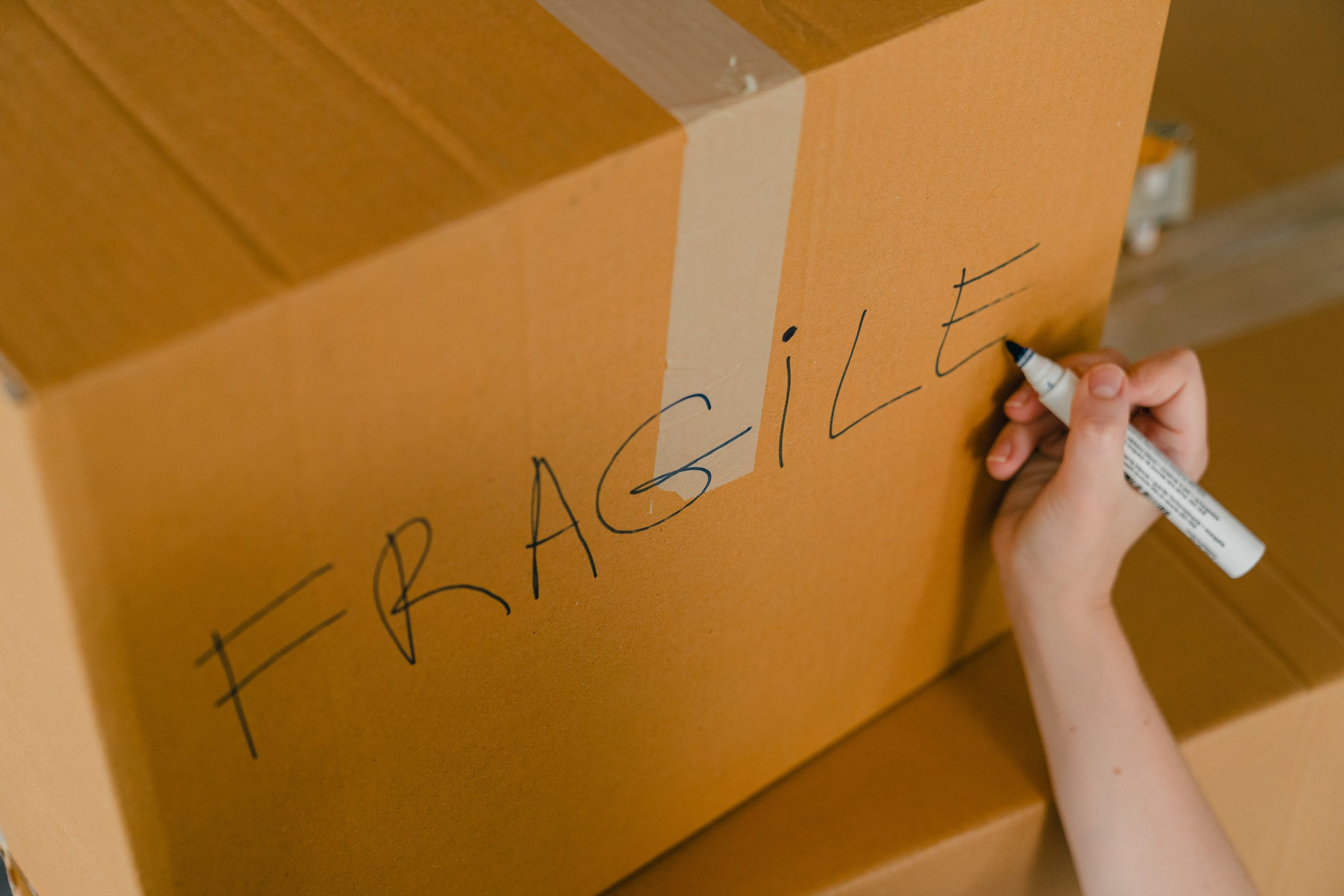 person-packing-box-with-fragile-items